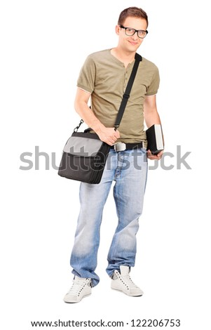Full length portrait of a male student with shoulder bag holding a book isolated on white background