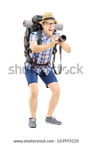 Full length portrait of a male tourist with backpack taking a picture with the camera isolated on white background - stock photo