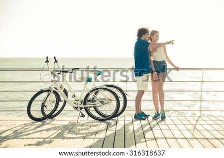 Full length portrait of a man and woman talking near bycicle outdoors