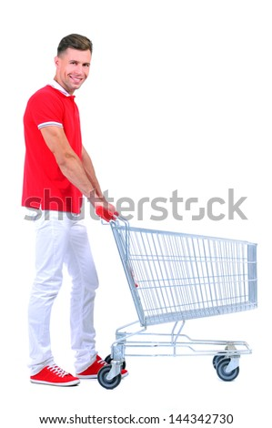 Full length portrait of a man posing next to an empty shopping cart isolated on white background - stock photo
