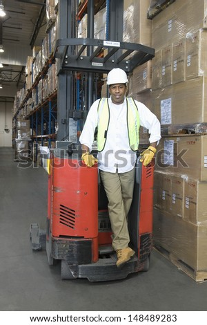 Full length portrait of a man standing with forklift truck in distribution warehouse