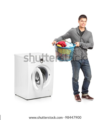 Full length portrait of a man with laundry basket posing next to a washing machine isolated on white background - stock photo