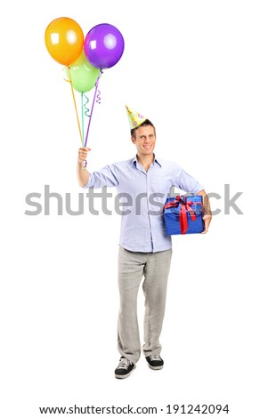 Full length portrait of a man with party hat holding balloons and a present isolated on white background