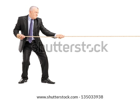 Full length portrait of a mature businessman in suit pulling a rope isolated on white background - stock photo