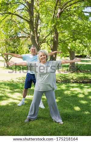 Full length portrait of a mature couple stretching hands at the park - stock photo