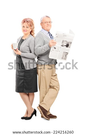 Full length portrait of a mature couple with a newspaper and cup of coffee isolated on white background - stock photo