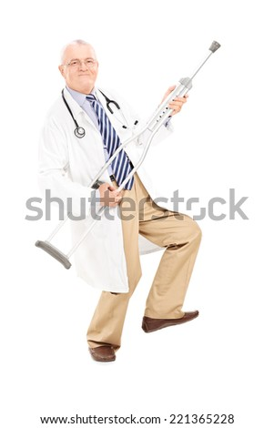 Full length portrait of a mature doctor playing guitar on a crutch isolated on white background - stock photo