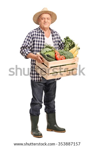 Full length portrait of a mature farmer carrying a wooden crate full of fresh vegetables and looking at the camera isolated on white background