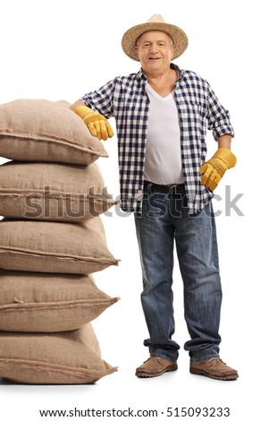 Full length portrait of a mature farmer leaning on a pile of burlap sacks isolated on white background