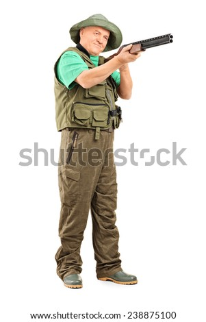 Full length portrait of a mature hunter aiming with a shotgun isolated on white background