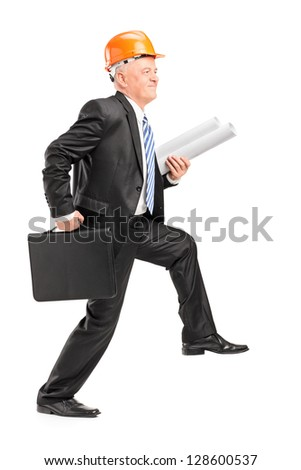 Full length portrait of a mature male architect with helmet holding blueprints and suitcase, walking with big steps isolated on white background