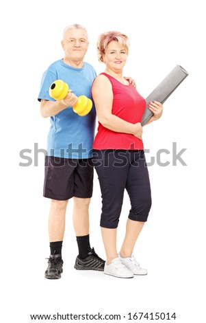 Full length portrait of a mature man and woman posing with dumbbell and mat isolated on white background