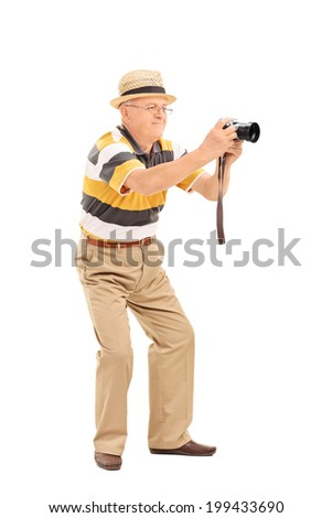 Full length portrait of a mature man taking a picture with a camera isolated on white background - stock photo