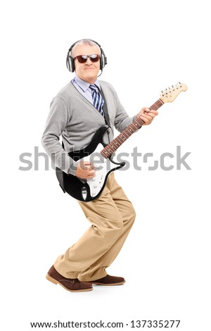 Full length portrait of a mature man with glasses playing guitar isolated on white background
