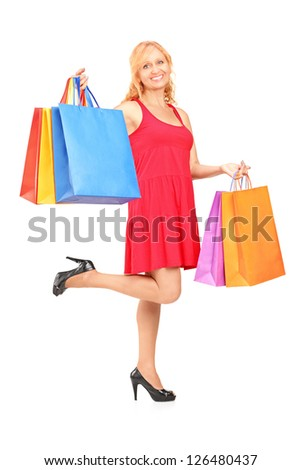 Full length portrait of a mature woman posing with shopping bags isolated on white background