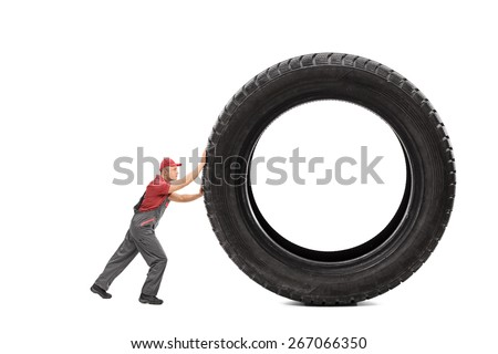 Full length portrait of a mechanic in a gray jumpsuit pushing a giant black tire isolated on white background - stock photo
