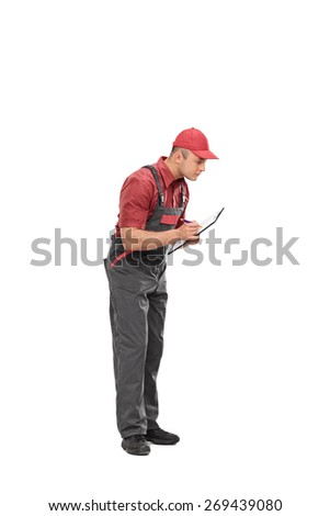 Full length portrait of a mechanic in a gray jumpsuit writing down notes on a clipboard isolated on white background - stock photo