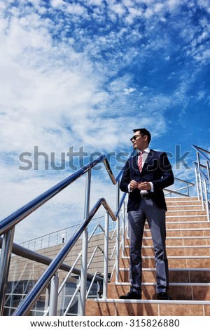 Full length portrait of a men entrepreneur dressed in luxury suit smoking a cigarette while standing on the steps against sky with copy space, businessman relaxing outside the office during work break - stock photo