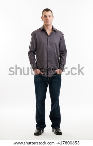Full length portrait of a mid 30s casual business man with hands in pockets isolated on a white background