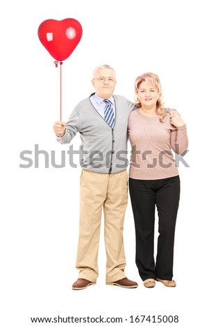 Full length portrait of a middle aged couple in hug holding a red heart balloon isolated on white background - stock photo