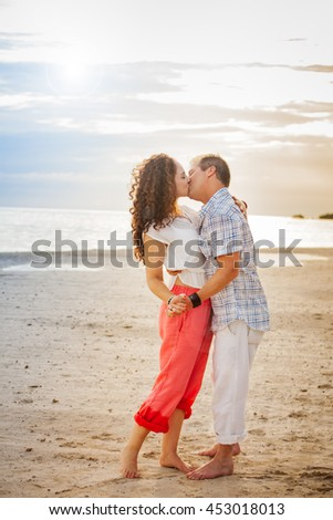 Full length portrait of a middle aged couple kissing on the beach at sundown in Jamaica
