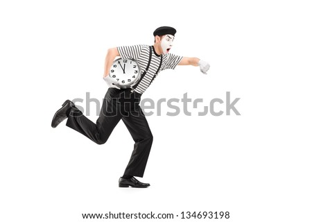 Full length portrait of a mime artist holding a clock and running late, isolated on white background - stock photo