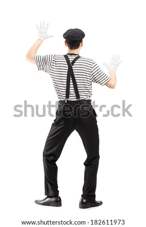 Full length portrait of a mime artist performing isolated on white background, rear view