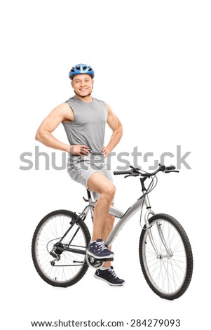 Full length portrait of a muscular young man posing seated on a bicycle with a blue helmet on his head isolated on white background