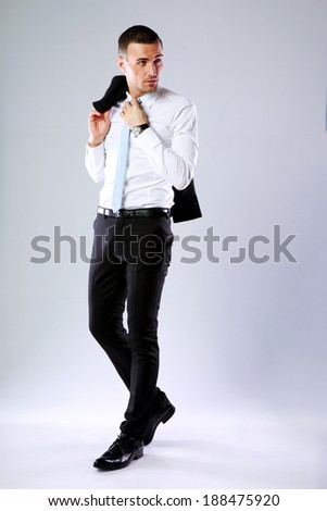 Full length portrait of a pensive business man holding jacket on shoulder on gray background - stock photo