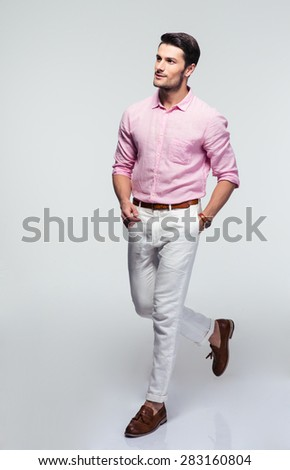 Full length portrait of a pensive businessman in shirt walking over gray background and looking away - stock photo