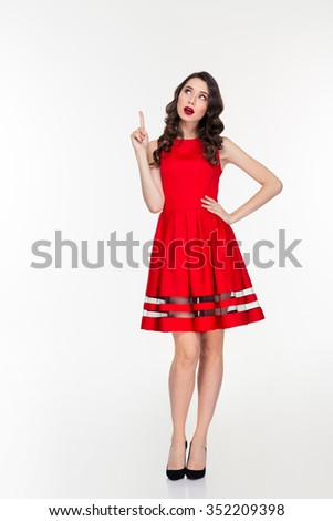 Full length portrait of a pensive woman in red dress pointing finger up isolated on a white background - stock photo