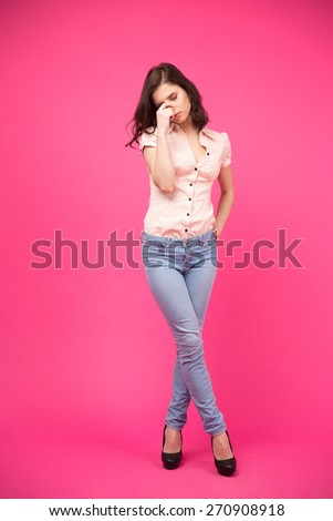 Full length portrait of a pensive woman standing over pink background. Wearing in jeans and shirt - stock photo