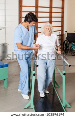 Full length portrait of a physical therapist assisting tired senior woman on walking track at hospital gym - stock photo
