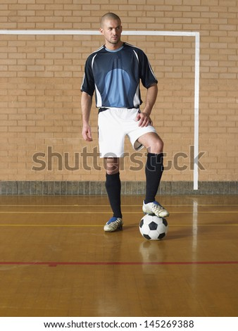 Full length portrait of a player with leg on football - stock photo