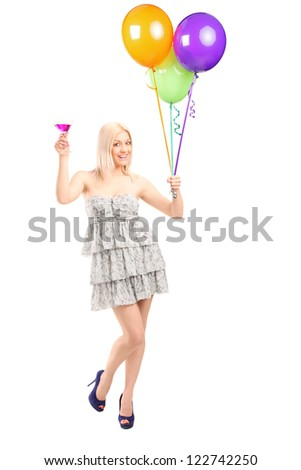 Full length portrait of a pretty blond female holding balloons and cocktail isolated on white background - stock photo