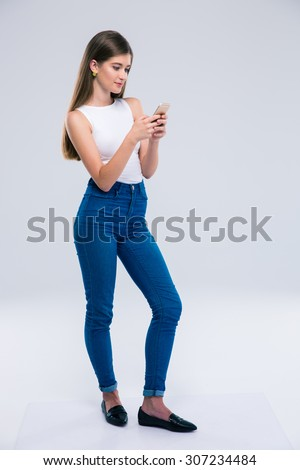 Full length portrait of a pretty female teenager using smartphone isolated on a white background - stock photo