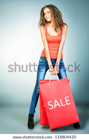 Full length portrait of a pretty girl with shopping bags. - stock photo