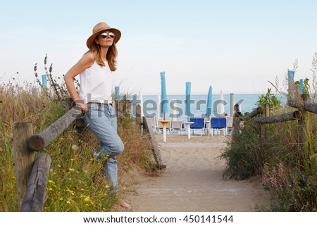 Full length portrait of a pretty mature woman wearing straw hat and sunglasses while relaxing by the sea.