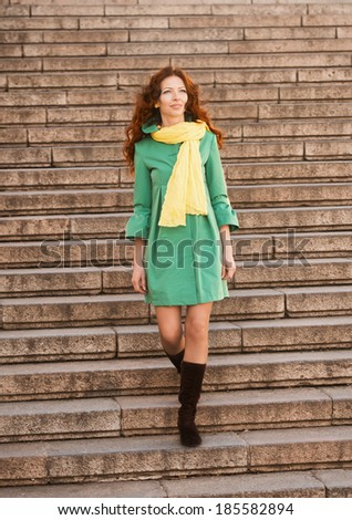 Full-length portrait of a pretty woman in green overcoat descending stairs - stock photo