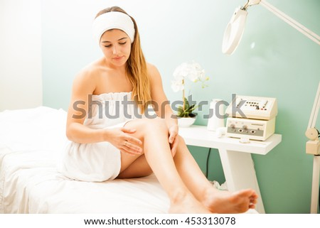 Full length portrait of a pretty young brunette looking at her perfect skin after spending a day at a beauty spa - stock photo
