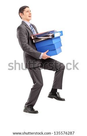 Full length portrait of a professional man carrying heavy folders, isolated on white background