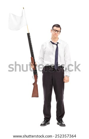 Full length portrait of a sad guy holding a rifle with white flag attached on it isolated on white background - stock photo