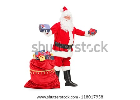 Full length portrait of a Santa Claus giving gifts next to a bag full of presents isolated against white background - stock photo
