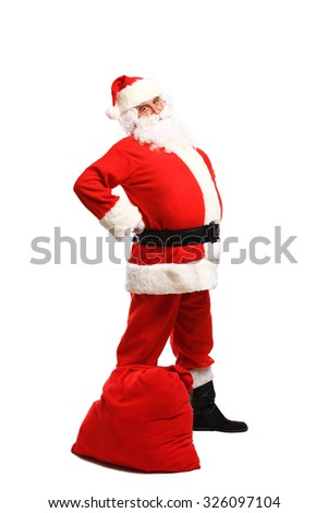 Full length portrait of a Santa Claus posing near a bag full of gifts isolated on white background