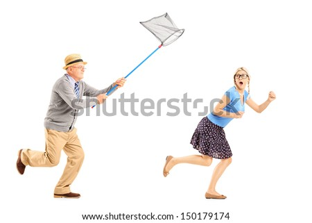 Full length portrait of a scared young female trying to runaway from mature man with butterfly net isolated on white background - stock photo