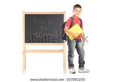 Full length portrait of a school boy with backpack and notebook standing next to a school board isolated on white background