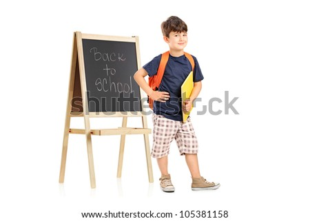 Full length portrait of a school boy with backpack posing next to a blackboard isolated on white background - stock photo