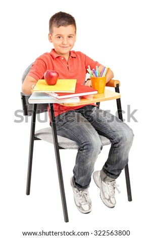 Full length portrait of a schoolboy sitting at a school desk with a few books and an apple on it isolated on white background