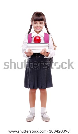 Full length portrait of a schoolgirl in uniform standing on white background and holding books and apple - stock photo