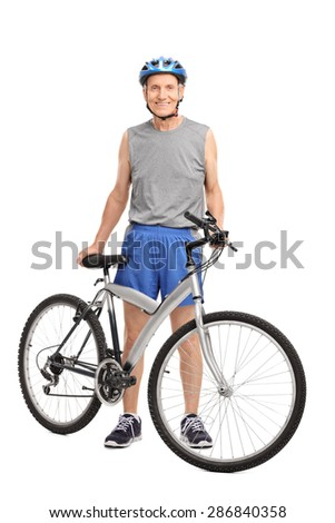 Full length portrait of a senior biker standing behind a bicycle and smiling isolated on white background